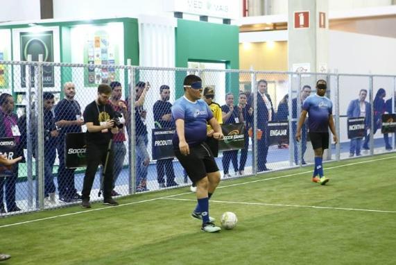 Na lateral do campo o atleta Bruno Gabriel prepara-se para chutar a bola. Do seu lado direito está o atleta Gustavo Costa. Atrás dele um fotógrafo manuseando a câmera. Ao fundo há um alambrado com algumas placas, e muitas pessoas assistindo.